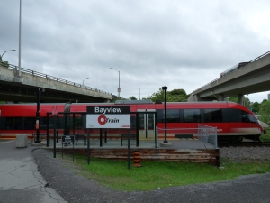 The O-Train stops at the Bayview station. Above to the right, a bus traveling along a dedicated busway arrives at the adjacent transit centre.